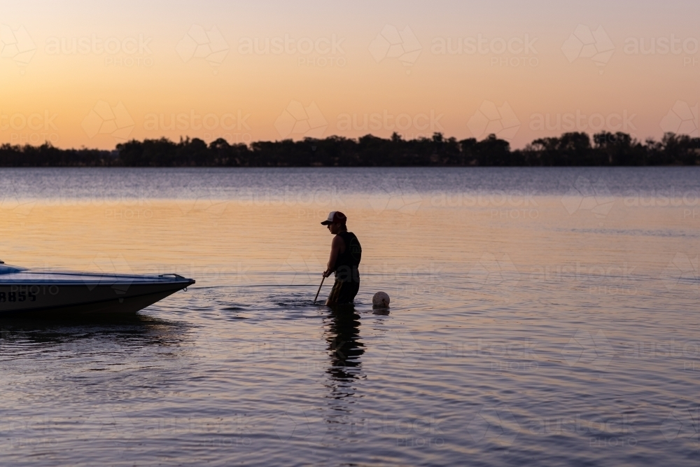 young person pulling up anchor of speedboat on lake - Australian Stock Image