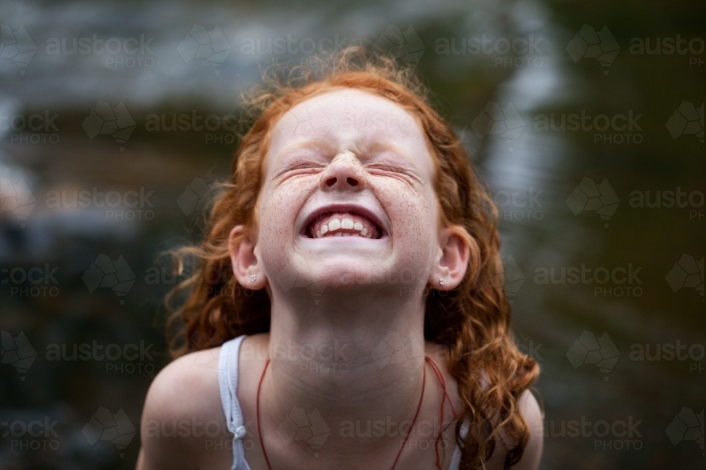 Young redhead girl laughing by the riverside - Australian Stock Image