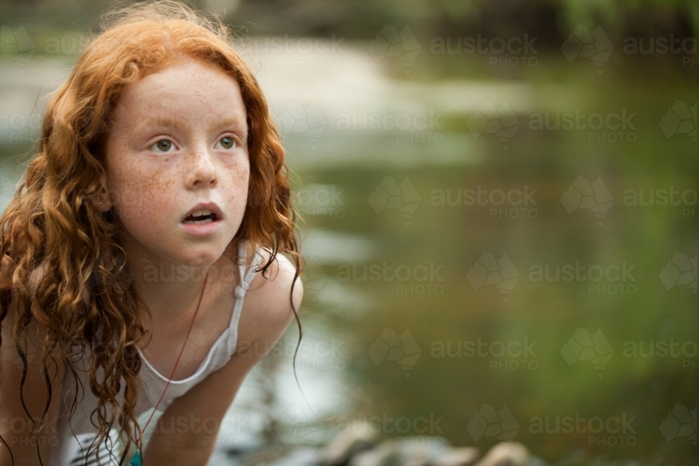 Young redheaded girl by the riverside - Australian Stock Image