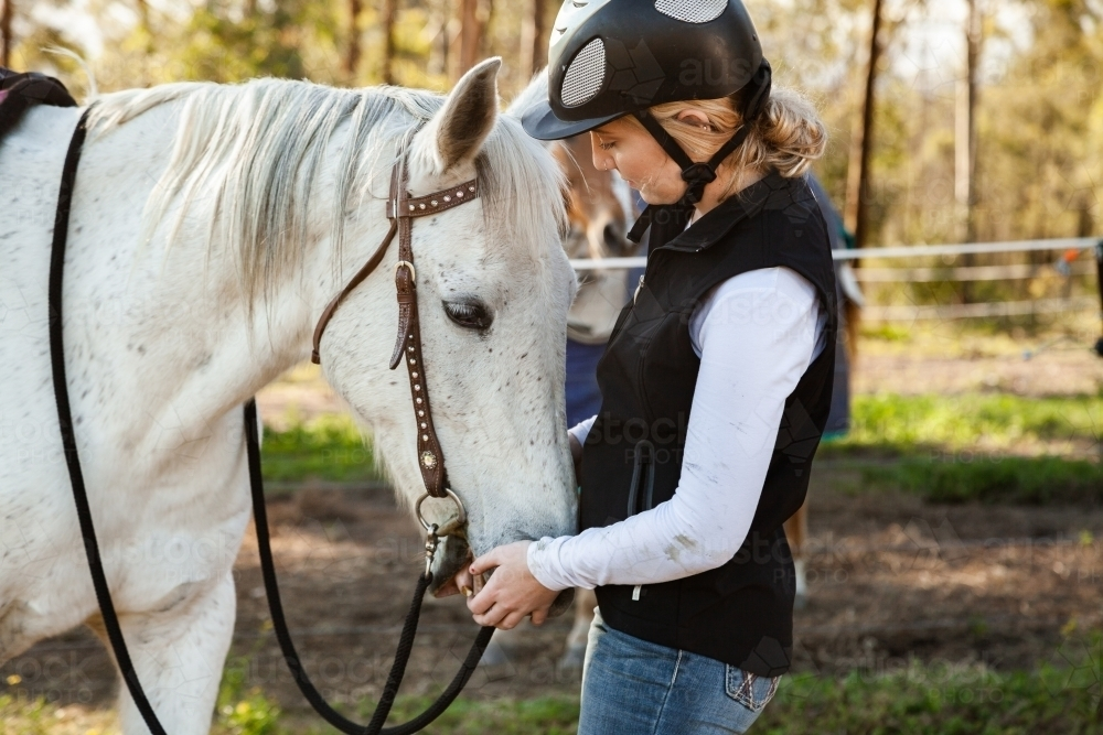 Young rider wearing a horse riding helmet while with her pet horse - Australian Stock Image