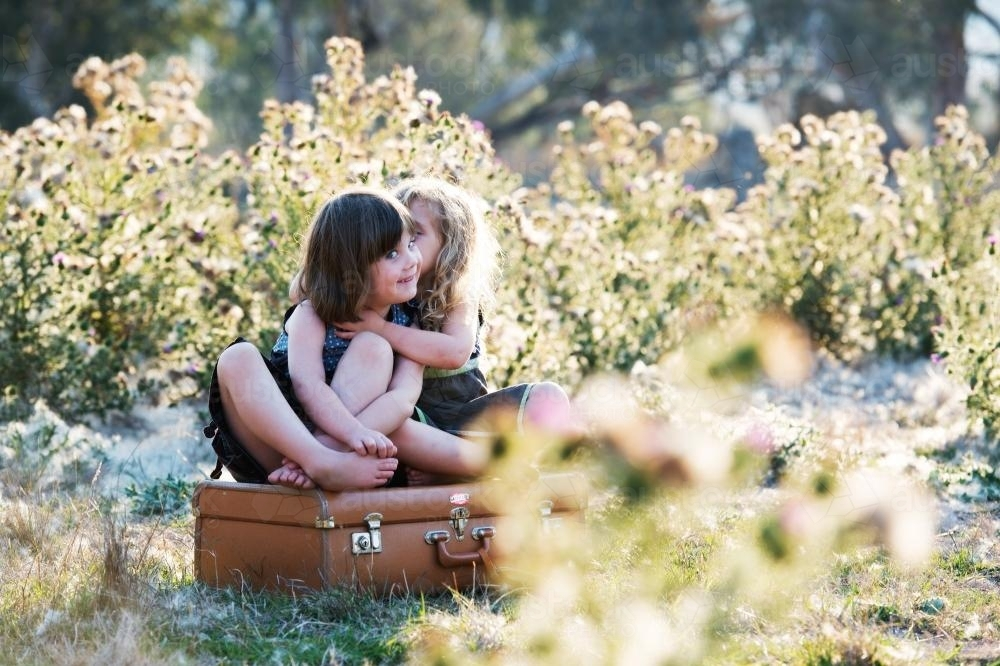 Young sisters sitting on a suitcase hugging - Australian Stock Image