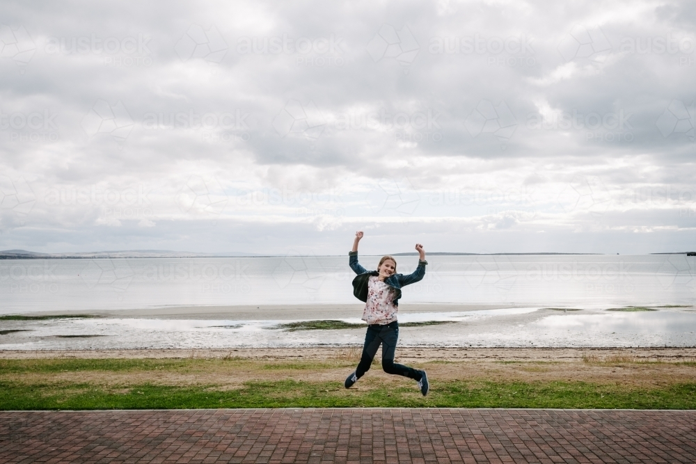 young teen girl jumping, ocean in the background - Australian Stock Image