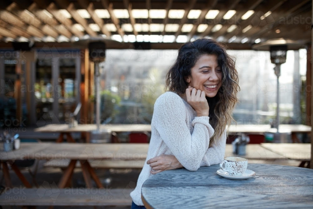 Young Turkish woman drinking coffee at cafe - Australian Stock Image