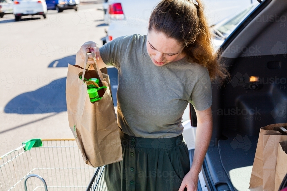 Young woman doing the shopping and loading paper bags into car from click and collect order - Australian Stock Image