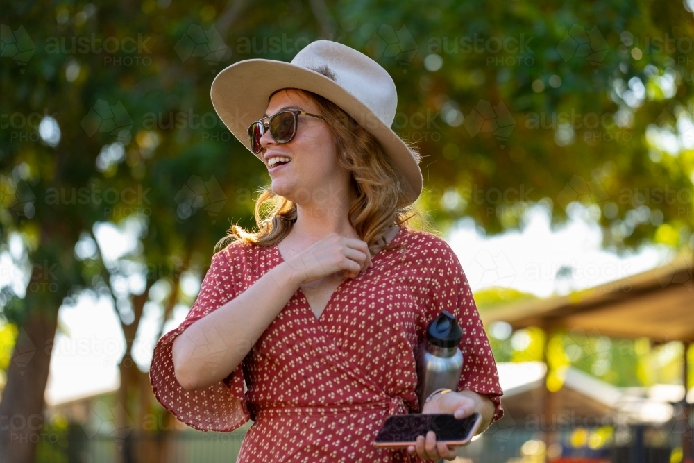 Young woman going to event wearing hat and sunglasses, carrying phone and water bottle - Australian Stock Image