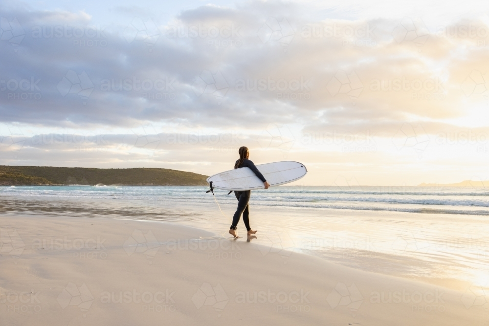 young woman heading into the surf carrying long board - Australian Stock Image