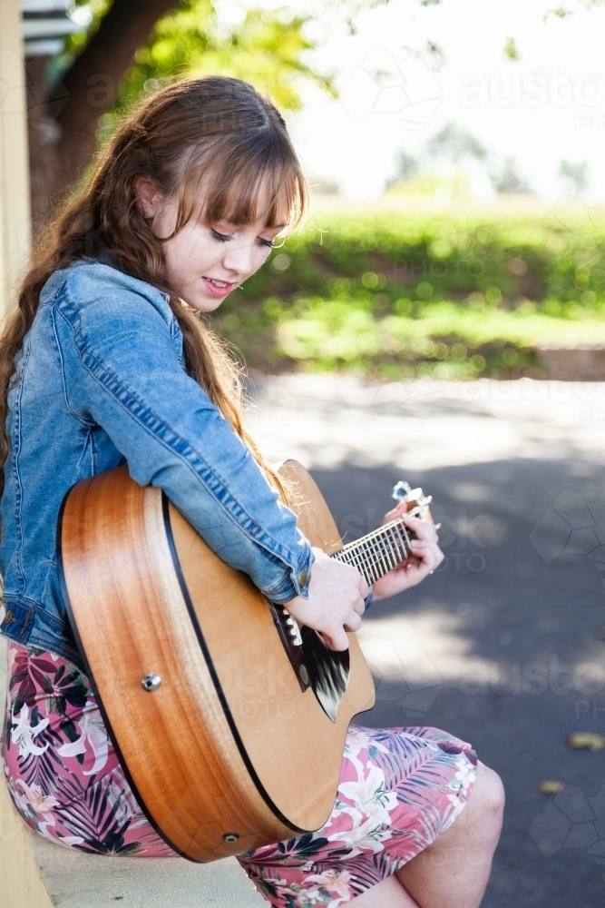 Young woman looking down playing guitar outside - Australian Stock Image