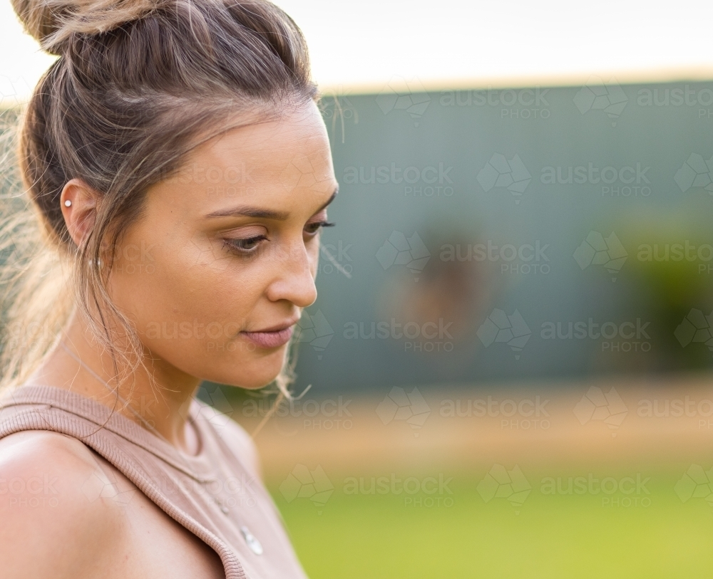 young woman looking down with hair in messy bun - Australian Stock Image