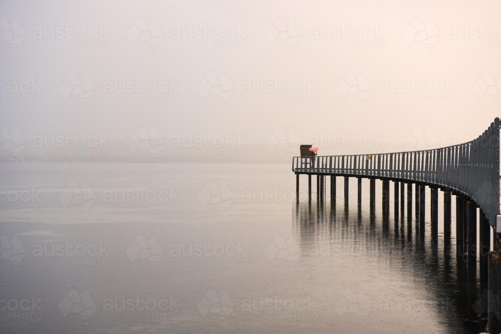 Young woman on curved jetty in the rain - Australian Stock Image