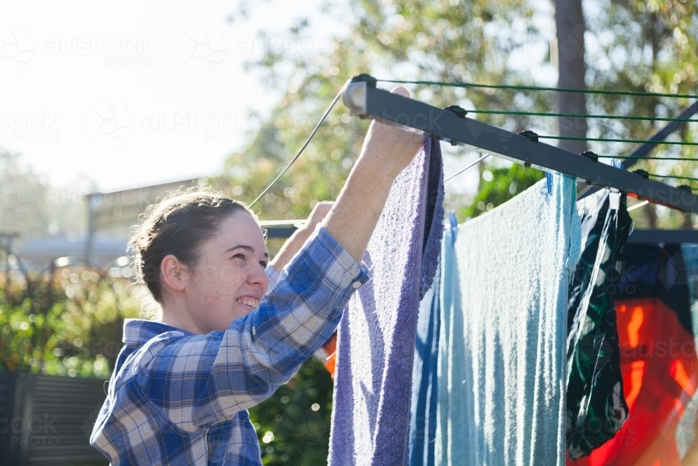 Image of Young woman pegging clothes to washing line in