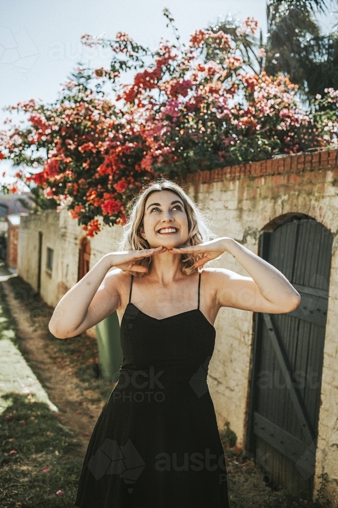 young woman smiling in a flower covered alleyway - Australian Stock Image