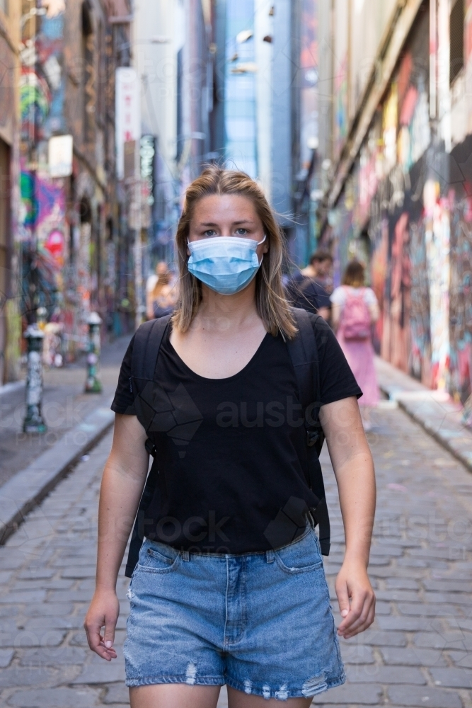 Young Woman Wearing a Face Mask Exploring Melbourne Lanes - Australian Stock Image
