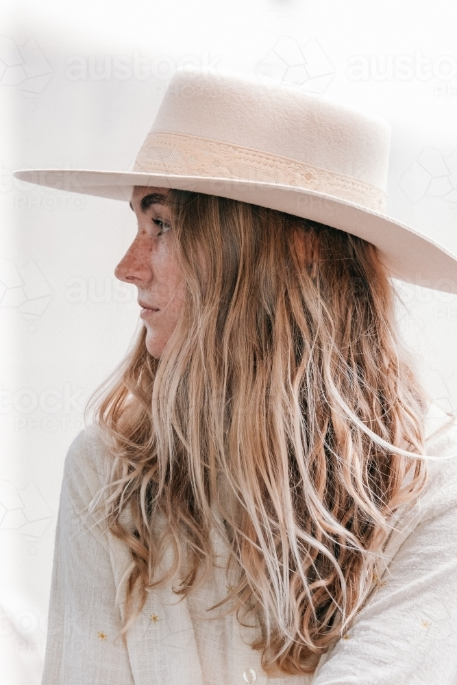 Young womens profile wearing a hat. - Australian Stock Image