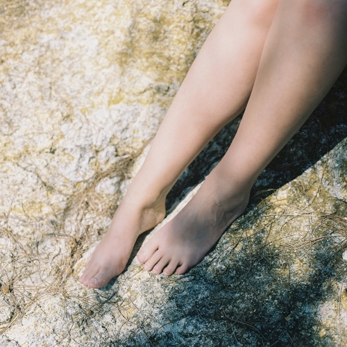 Woman's Naked Legs on Beach Rock