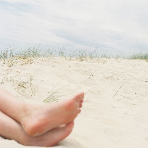 Cropped shot of bare feet on a sandy beach