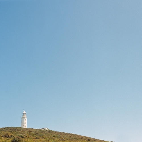 Lighthouse in the distance on a headland with blue sky background