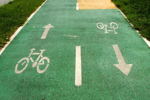 Bicycle and arrow signs painted in white on green asphalt