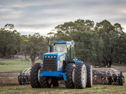 Tractor with air-seeder sowing crop in a paddock