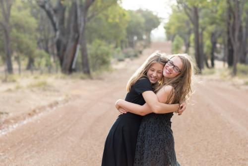 Happy teenage girls hugging in country landscape