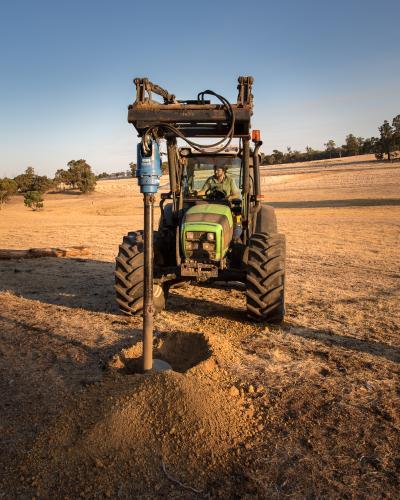 Digging a hole with hydraulic posthole digger on tractor