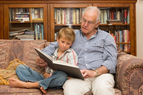 Grandfather and grandson reading a book on a sofa together