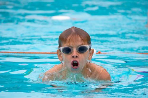 Young boy wearing goggles swimming breaststroke in swimming pool
