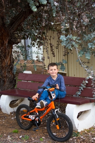 Young boy sitting on park bench with bike