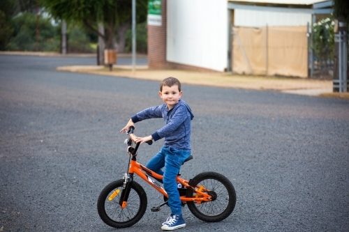 Little boy riding his bicycle on the street