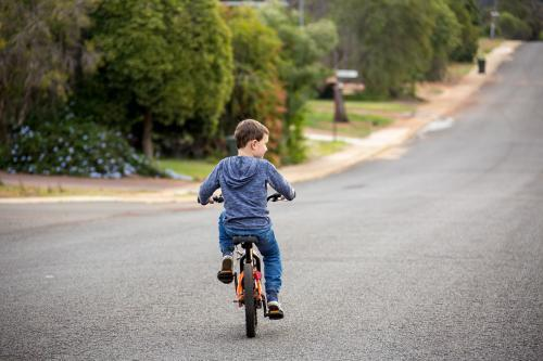 Child riding bike on road with no helmet