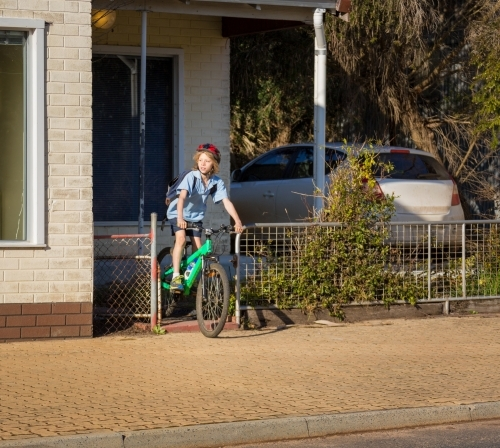 Schoolboy leaving home on bicycle