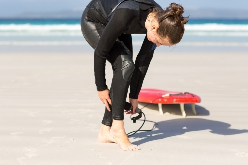 Surfer girl in wetsuit on the beach