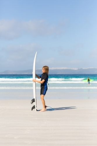 Young boy with surfboard on the beach
