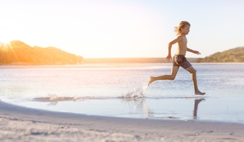 Blond-haired boy running through water on the beach