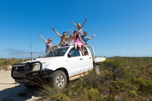 Young people having fun on roof of ute