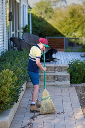 Boy in work clothes sweeping paved path