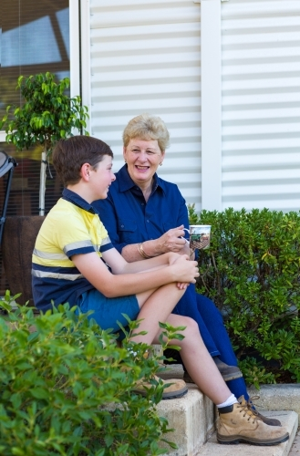 Boy sitting on step with grandmother