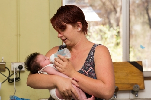 Young mother feeding infant with formula in a bottle