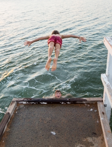 Kid diving off jetty into a lake