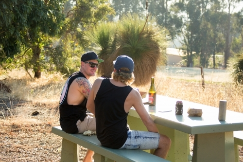 Two young blokes sitting drinking at picnic table outside