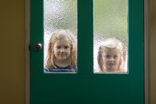 Two little girls outside looking in through door