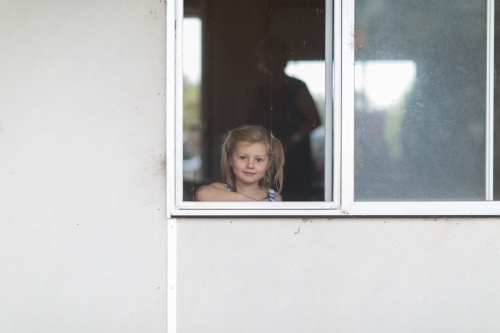 Child looking out window through flyscreen