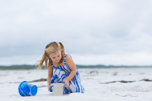 Child playing with bucket on beach
