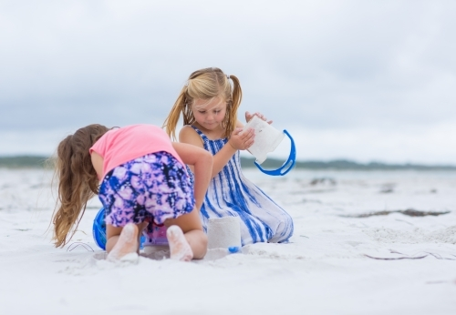 Two little girls building sandcastles on the beach