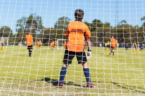 Young kid goal keeper behind net in soccer game