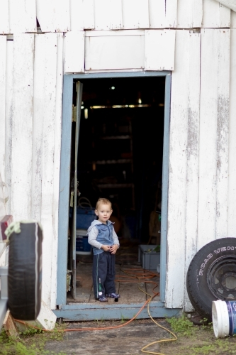 Toddler standing in doorway of shed