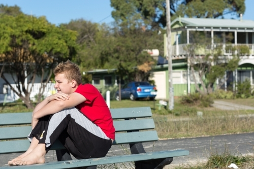 Teenage boy sitting on park bench with arms around knees