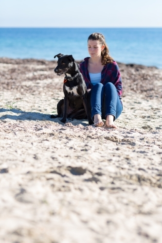 Girl sitting with dog on the beach