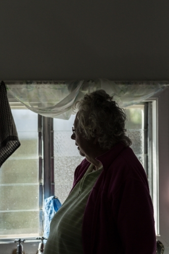 Elderly lady in gloomy room, looking out the window