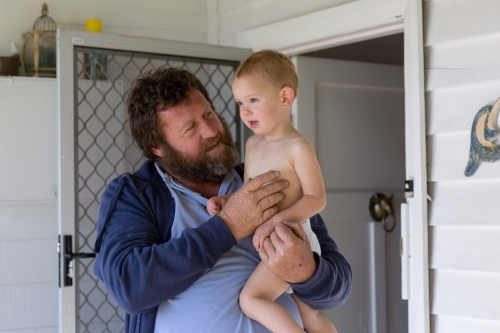 Bearded man holding child outside front door