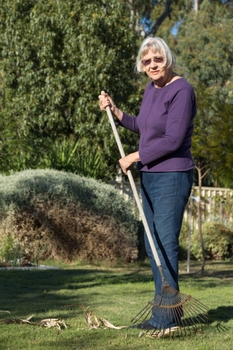 Older woman in garden with rake on lawn